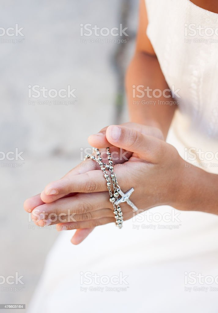 Girl praying with crucifix stock photo