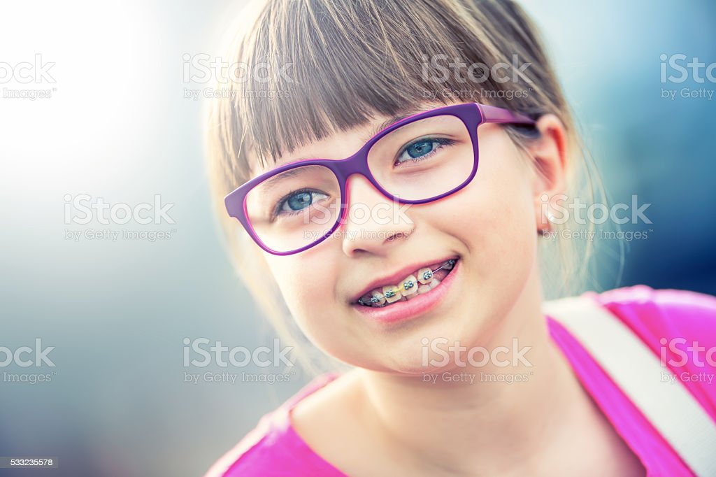 Girl. Pre teen. Girl with glasses. Girl with teeth braces. stock photo