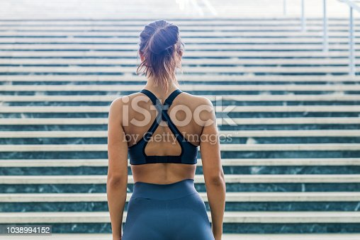 Rear view of fit young woman in sports clothing standing on steps in morning. Female with muscular body ready for workout outdoors. Photo of young woman standing by steps outdoors. Fitness woman before workout.