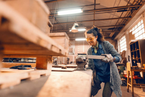 Girl prepares wooden plank for processing on carpenter bee, wearing protective equipment. Girl prepares wooden plank for processing on carpenter bee, wearing protective equipment. carving craft activity stock pictures, royalty-free photos & images
