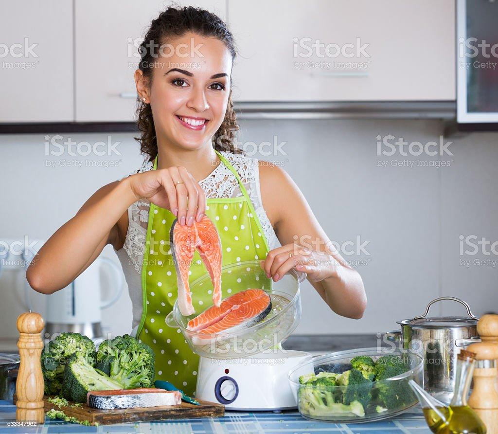 Garota preparação de peixes e legumes - foto de acervo