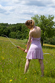 Young girl in a pink dress is doing archery on a spring meadow with flowers.See some similar pictures from my portfolio: