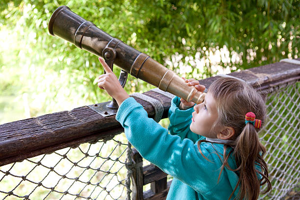 Girl preschooler discovers surroundings through old-style telescope stock photo