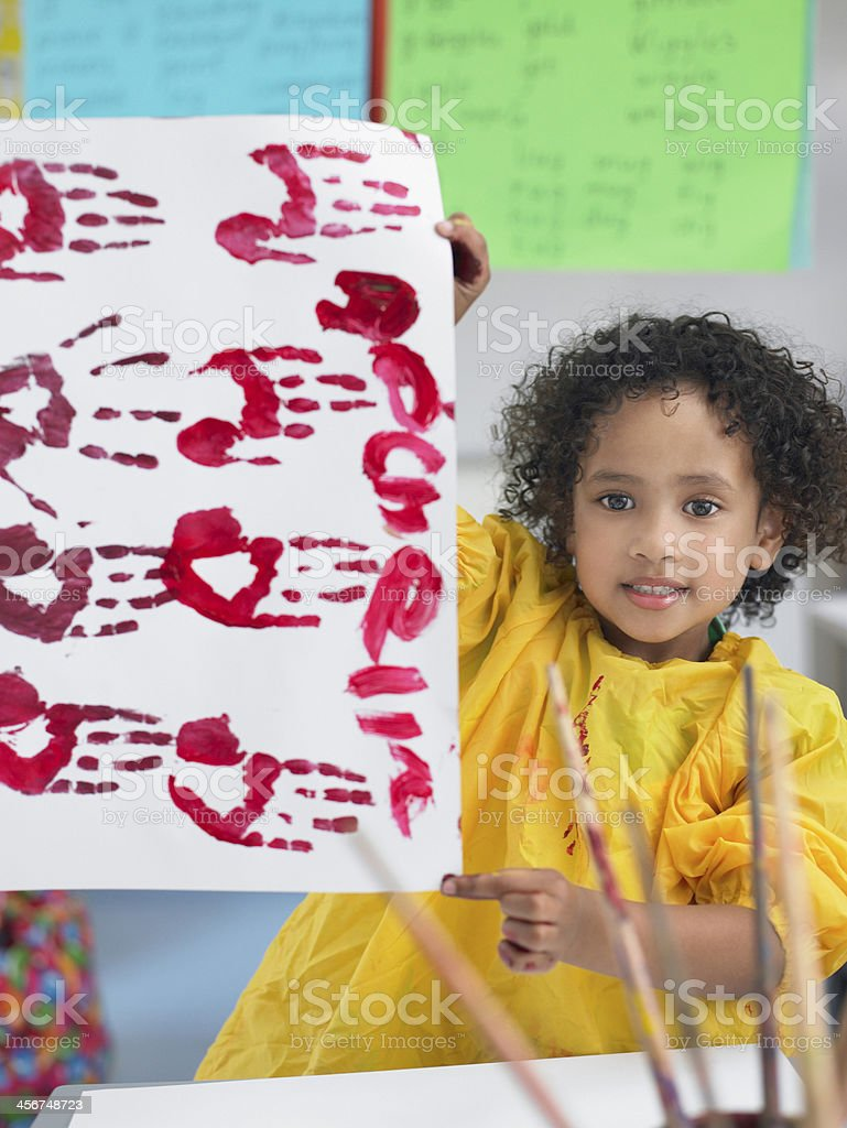 Girl Presenting His Finger Painting In Class stock photo