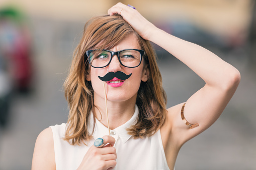 Girl pretending to be a man with mustache.