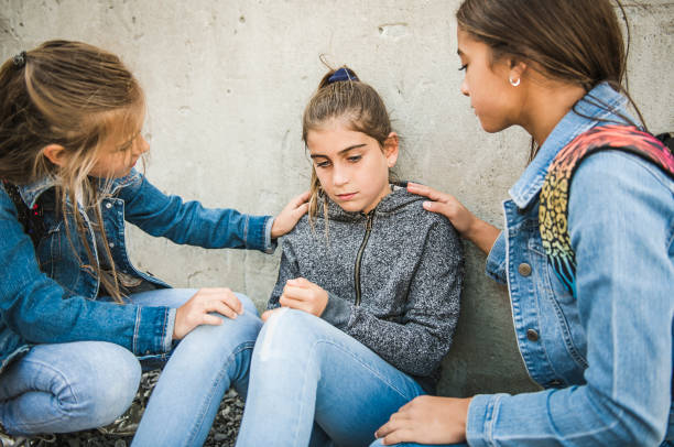 girl problem at school, sitting and consoling child each other stock photo