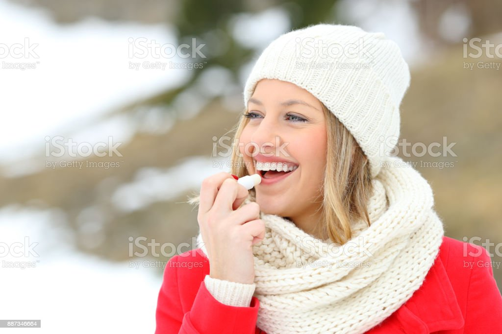 Girl protecting lips with lip balm in winter stock photo