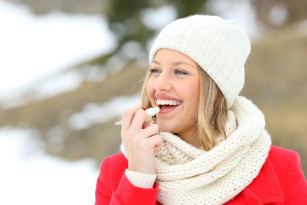 mädchen, die lippen mit lip balm im winter schützen - labello stock-fotos und bilder