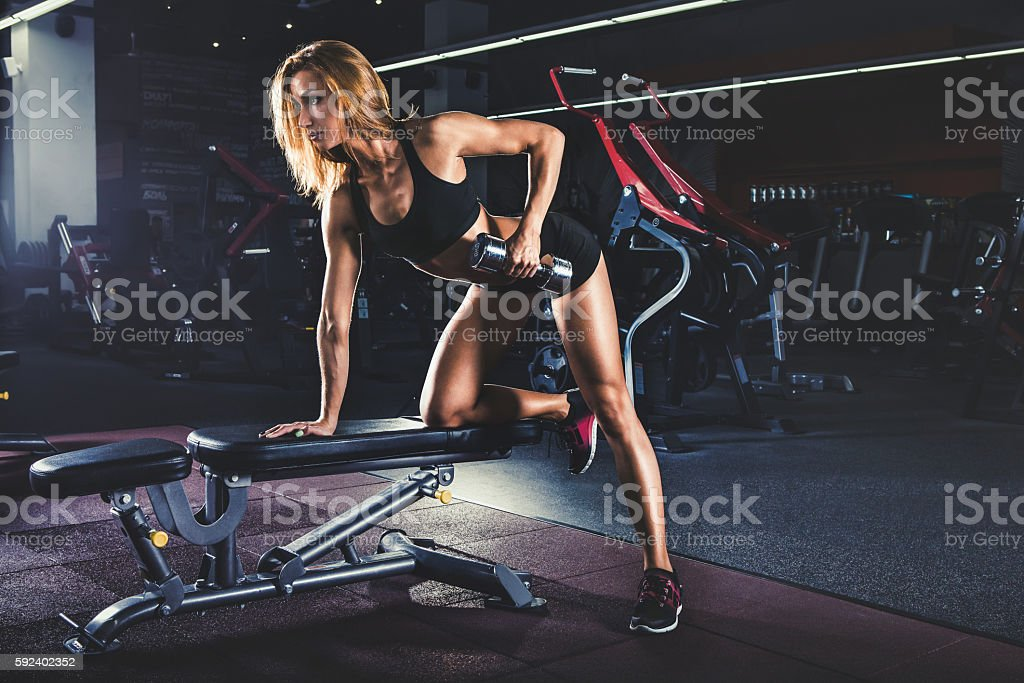Girl pumping up muscles with dumbbells – Foto