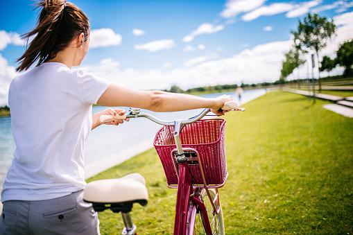 Girl pushing pink bike
