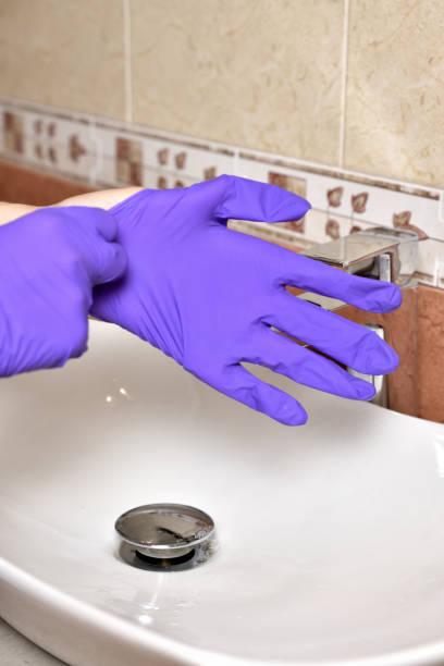 niña se pone guantes de protección durante la epidemia de coronavirus. el uso de guantes de protección en una epidemia. protección del coronavirus cóvido-19 - foto de stock