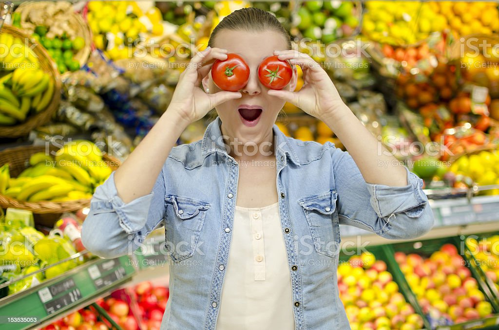 Girl puts to tomatoes in front of her eyes royalty-free stock photo