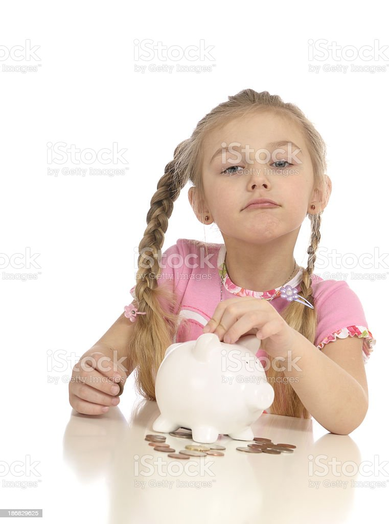 Girl putting coins in piggy bank royalty-free stock photo