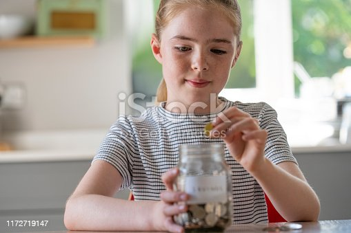 Girl Putting Coins Into Glass Jar Labelled Savings At Home