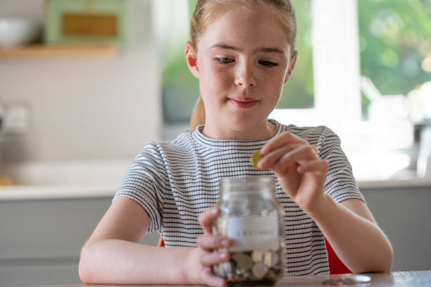 Girl Putting Coins Into Glass Jar Labelled Savings At Home Girl Putting Coins Into Glass Jar Labelled Savings At Home allowance stock pictures, royalty-free photos & images