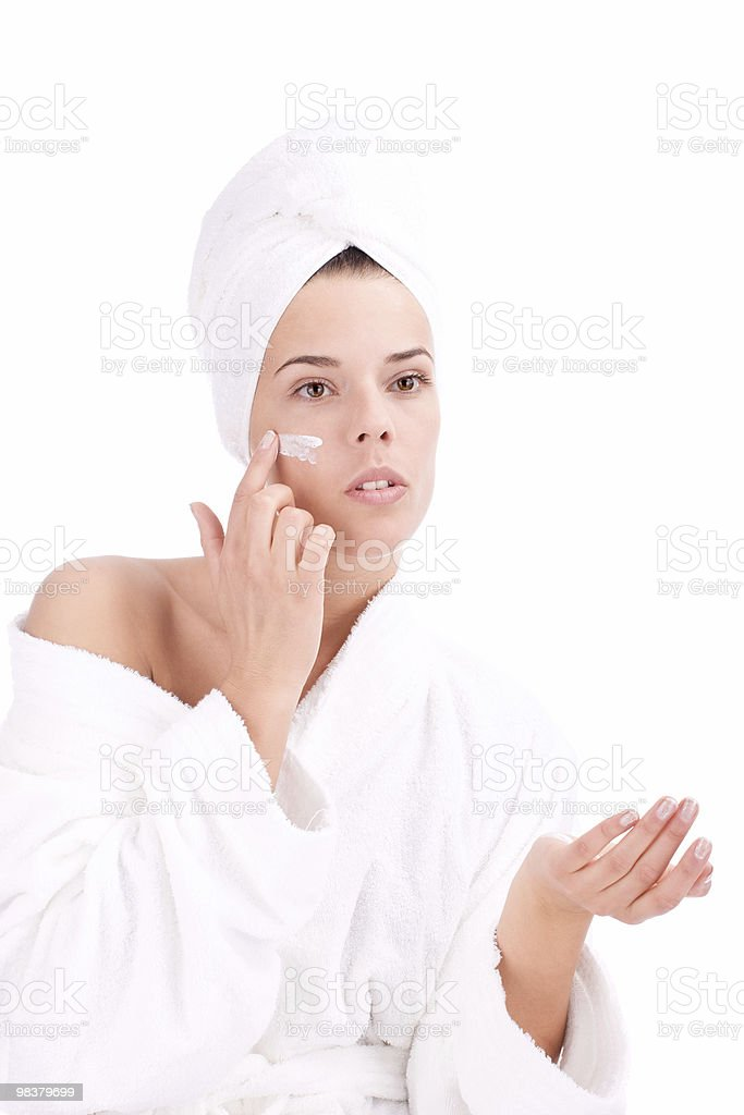 Girl putting cream on her face royalty-free stock photo