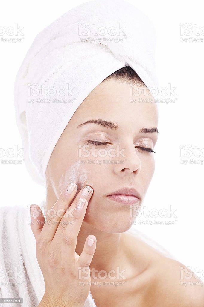 Ragazza mettendo la crema per il viso foto stock royalty-free