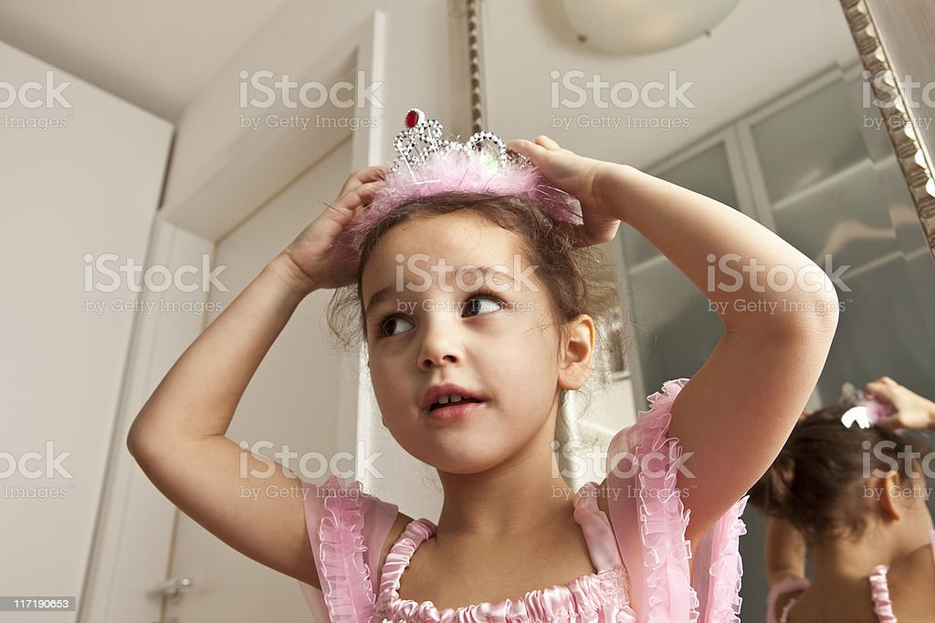 Girl putting crown on her head stock photo