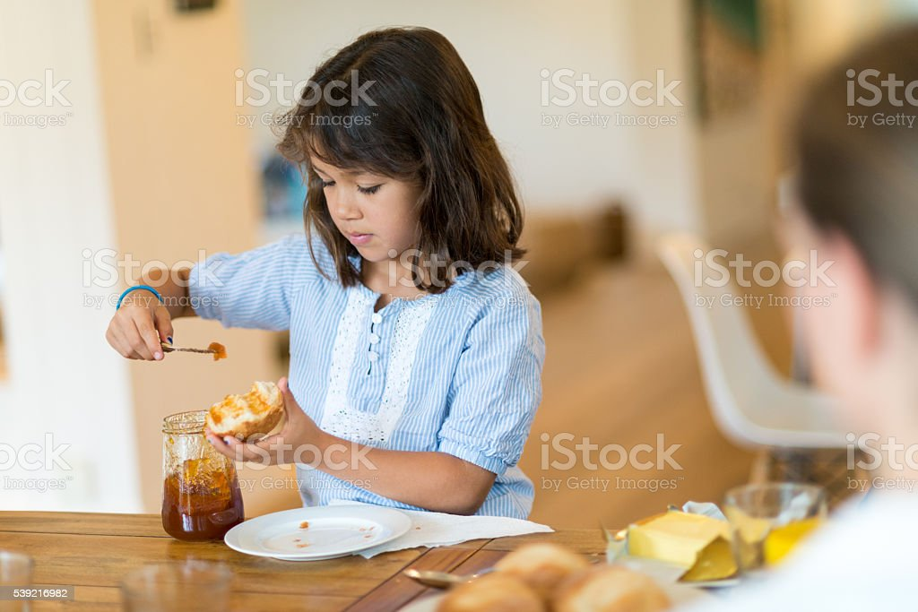 Girl putting marmalade on the bread stock photo
