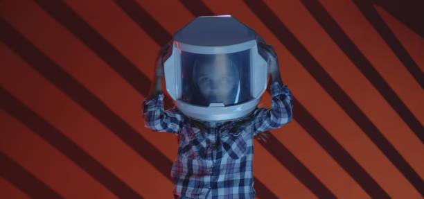 girl putting on oversized helmet - vr red background imagens e fotografias de stock