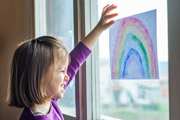 Girl putting picture of rainbow in window at home during coronavirus pandemic stock photo