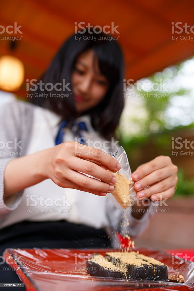 Girl putting soybean flour on Japanese confection royalty-free stock photo
