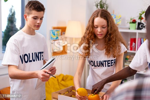 istock Girl putting vegetables and fruits into box gathering food for donation 1148048212