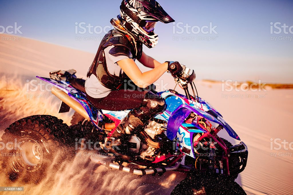 Girl quad racer in protective gear racing over sand dunes stock photo