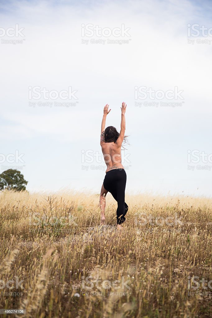 Girl raising arms and stands in countryside stock photo