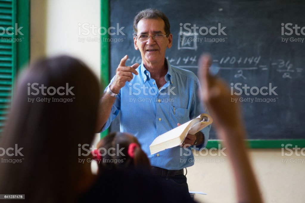 Girl Raising Hand Asking Question To Teacher At School - foto de stock