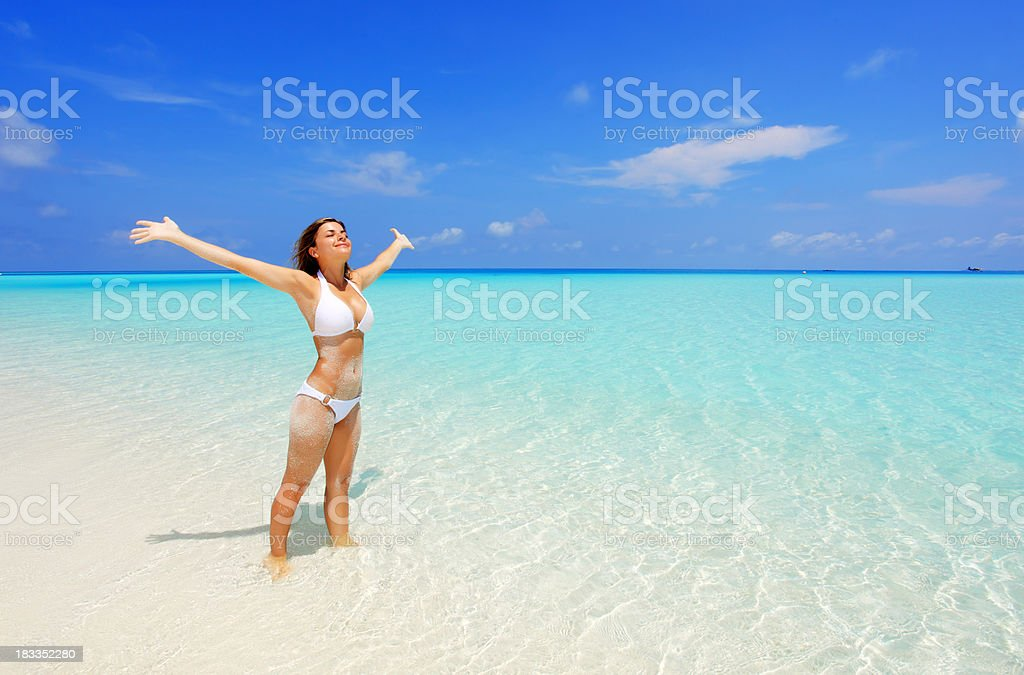 Girl raising hands, standing in the sea. royalty-free stock photo