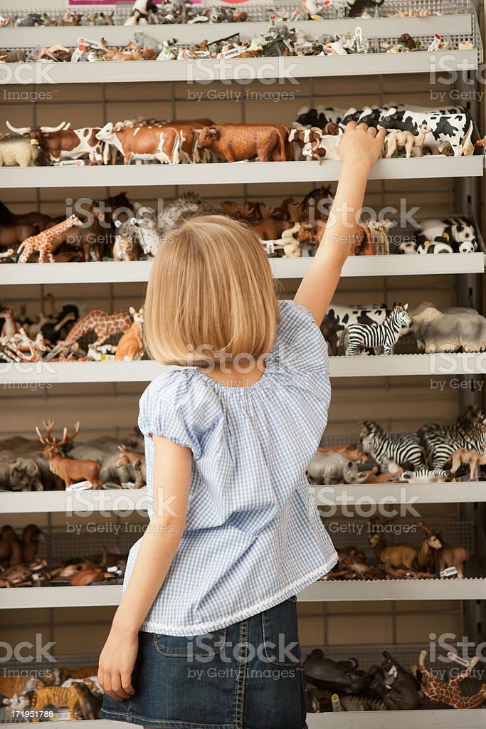 Girl reaching for plastic cow in toy store stock photo