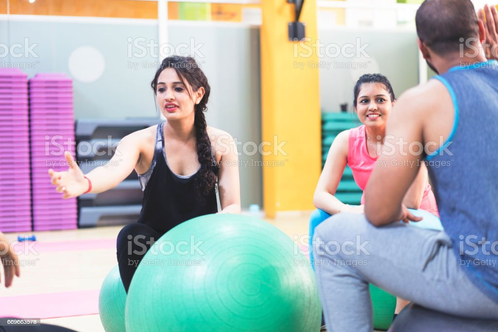 Girl reaching out to help for the student who is fallen down the exercise ball stock photo