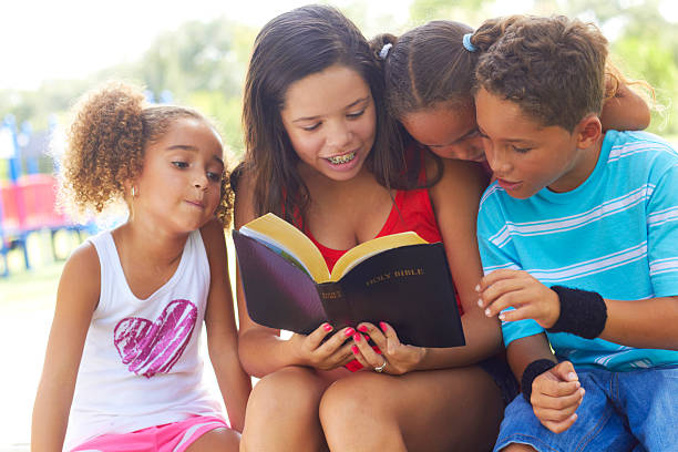 Girl reading a Bible to young siblings in an outdoor park stock photo