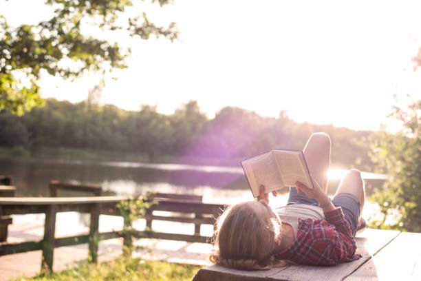 Girl reading a book at the lake stock photo