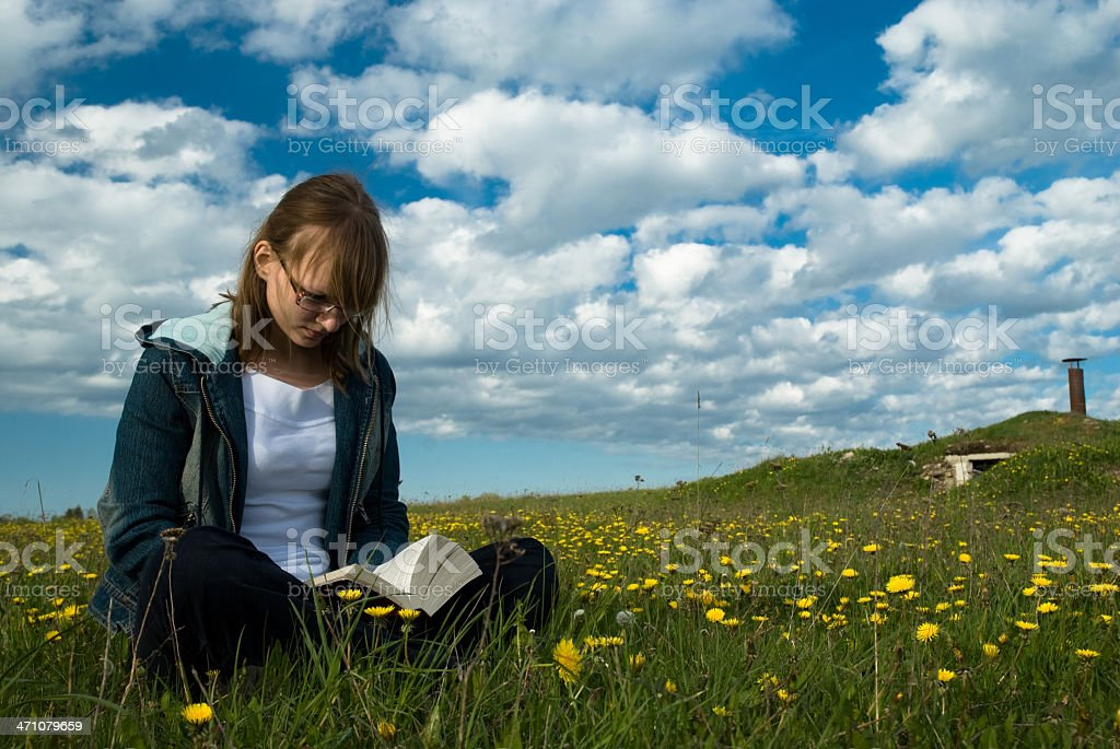girl reading a book in the meadow under  cloudy sky royalty-free stock photo