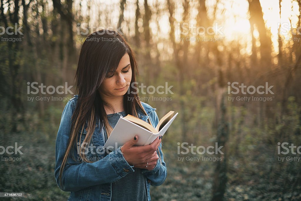 A girl reading a book in the woods stock photo