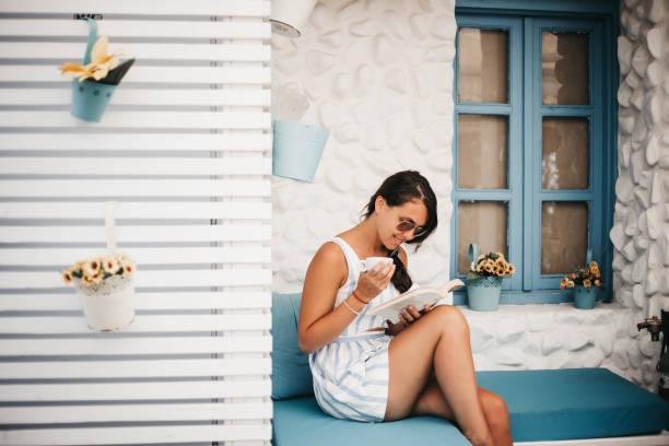 mädchen lesen ein buch auf dem balkon - natürliche make up kurse stock-fotos und bilder