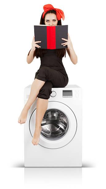 mädchen liest ein buch über eine waschmaschine - leise waschmaschine stock-fotos und bilder