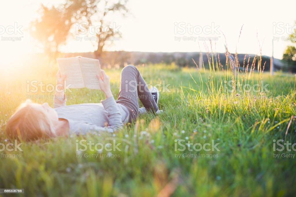 Girl reading a book outside header stock photo