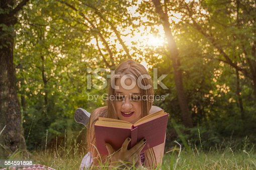 862602714 istock photo Girl reading a book 584591898