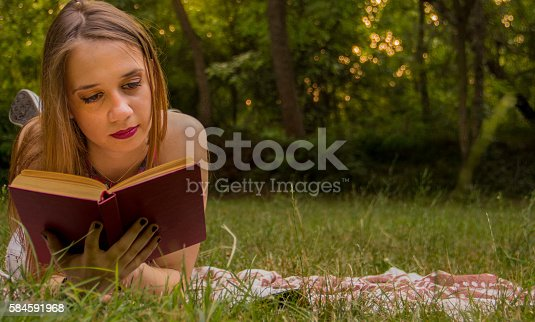 862602714 istock photo Girl reading a book 584591968