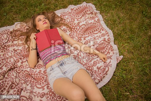 862602714 istock photo Girl reading a book 584592928