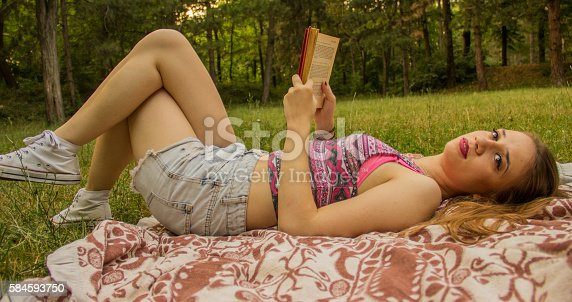 862602714 istock photo Girl reading a book 584593750