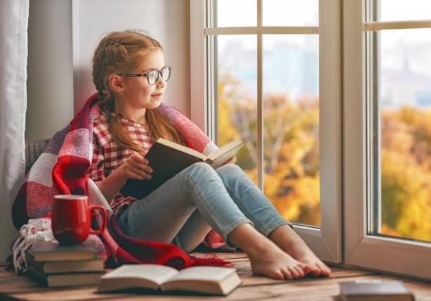 meisje het lezen van een boek - a little girl reading a book stockfoto's en -beelden