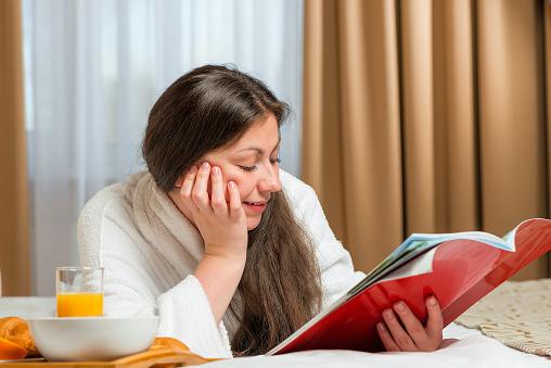 683349444 istock photo girl reading an interesting magazine on bed in bathrobe 478365268