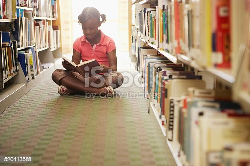 istock Girl reading at the library 520413588