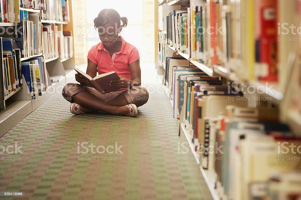 Girl reading at the library - foto de stock