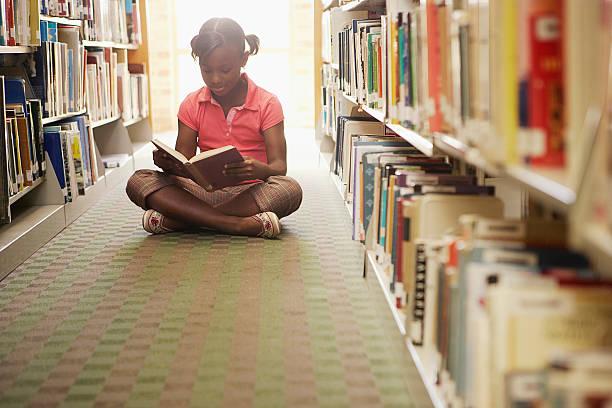 girl reading at the library - a little girl reading a book stockfoto's en -beelden