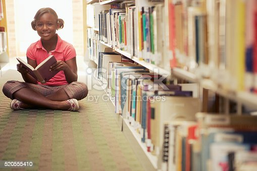 istock Girl reading at the library 520555410